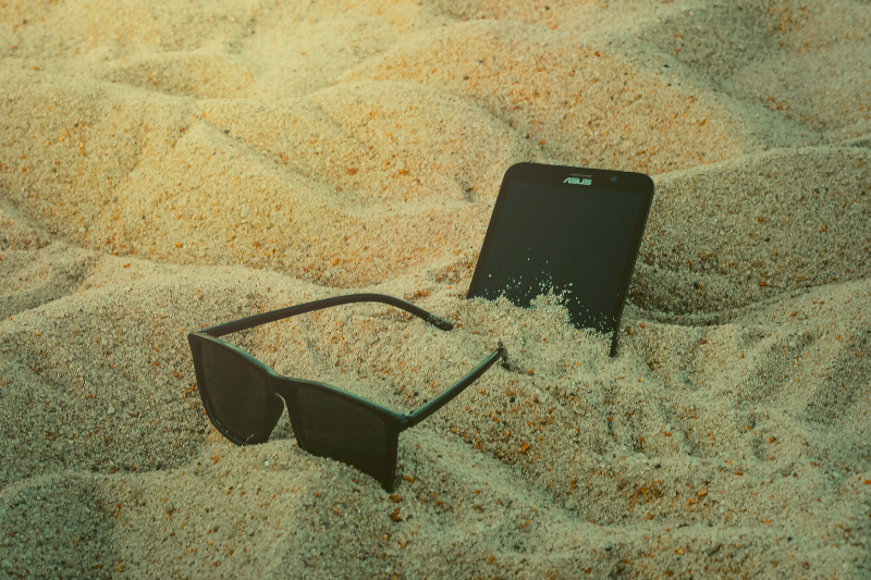 Smartphone and sunglasses in sand during summer