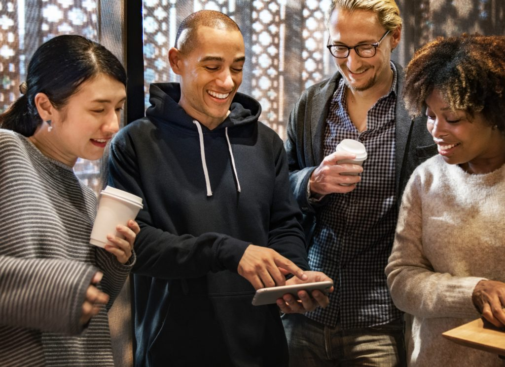 group of strangers/friends looking at the phone and smiling